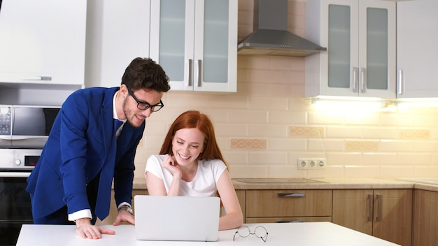 Young business couple talking and using laptop in kitchen at home.