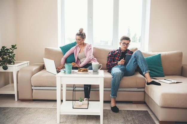 Молодая деловая пара в очках работает за ноутбуком, ест бутерброды и учится удаленно