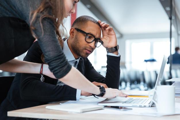 Молодая бизнес-команда, работающая с новым ноутбуком для запуска проекта в офисе