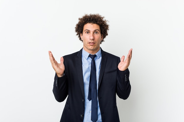 Young business curly man against white background surprised and shocked.