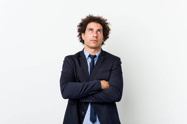 Young business curly man against white background tired of a repetitive task.