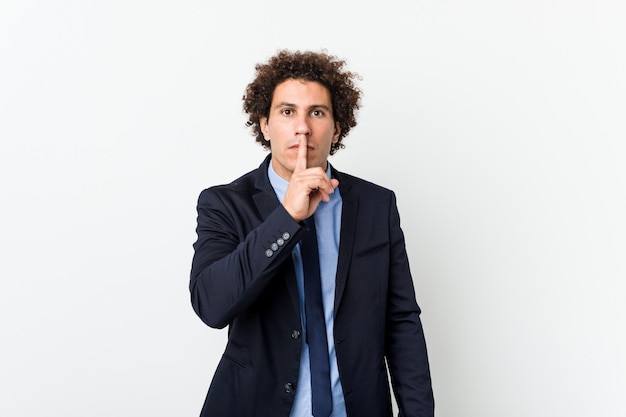 Young business curly man against white keeping a secret or asking for silence.