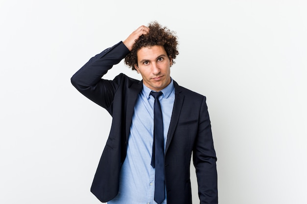 Young business curly man against white wall being shocked, she has remembered important meeting.
