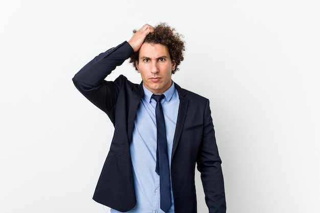 Young business curly man against white wall tired and very sleepy keeping hand on head.
