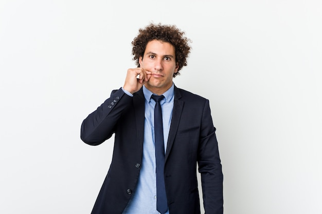Young business curly man against white wall with fingers on lips keeping a secret.