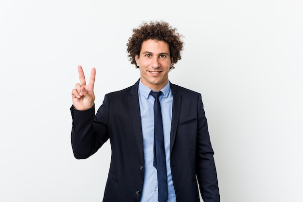 Young business curly man on white showing victory sign and smiling broadly.