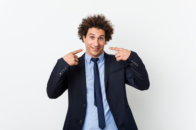 Young business curly man on white smiles, pointing fingers at mouth.