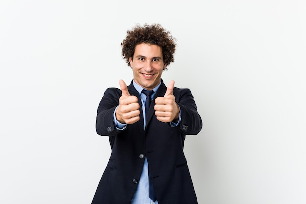 Young business curly man on white with thumbs ups, cheers about something, support and respect concept.