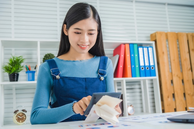 Young business female calculating family budget, trying to save some money with financial paper bill.