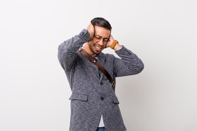 Молодой деловой филиппинский мужчина у белой стены радостно смеется, держась за голову. концепция счастья.