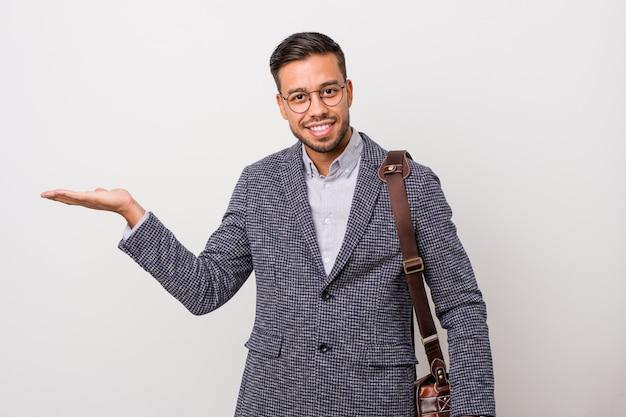 手のひらにコピースペースを示し、腰に別の手を保持している白い壁に若いビジネスフィリピン人男性。