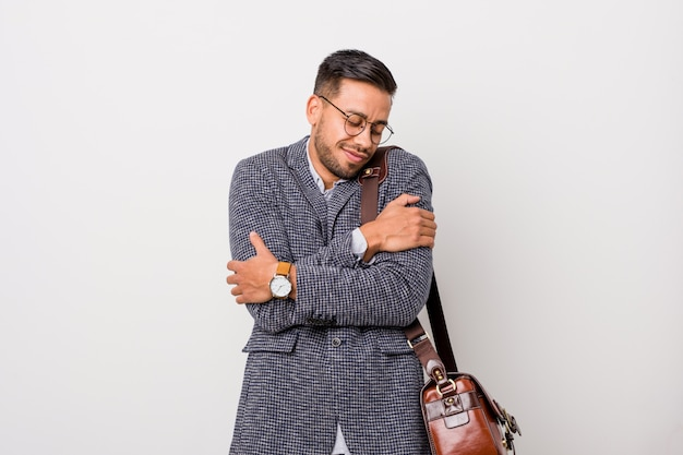 Young business filipino man against a white wall hugs, smiling carefree and happy.