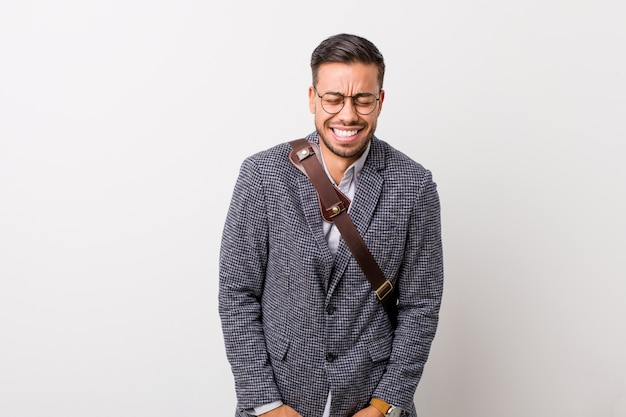 Young business filipino man against a white wall laughs and closes eyes, feels relaxed and happy.