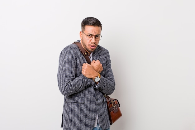 Young business filipino man against a white wall scared and afraid