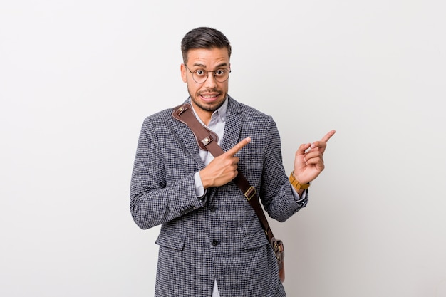 Young business filipino man against a white wall shocked pointing with index fingers to a copy space.