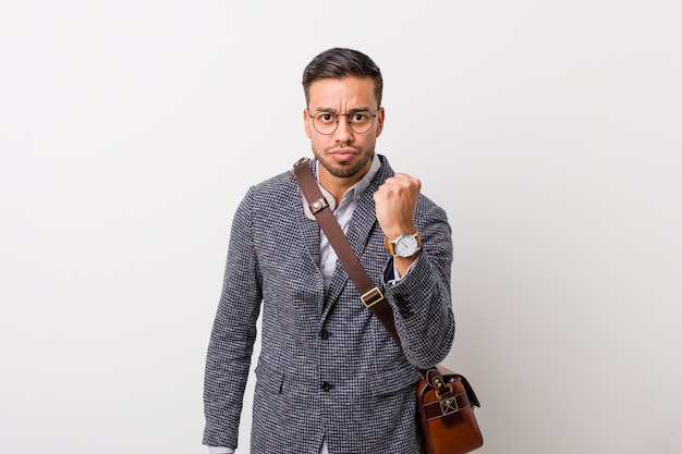 Young business filipino man against a white wall showing fist to camera, aggressive facial expression.