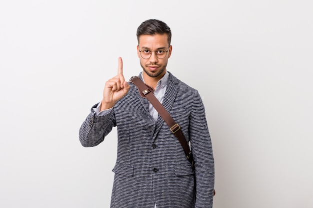 Young business filipino man against a white wall showing number one with finger.