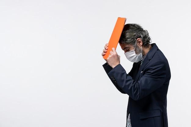 スーツを着て、白い背景にサージカルマスクを身に着けている彼の頭に彼の文書を保持している若いビジネス男