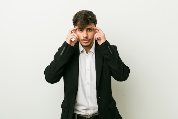 Young business hispanic man focused on a task, keeping forefingers pointing head.