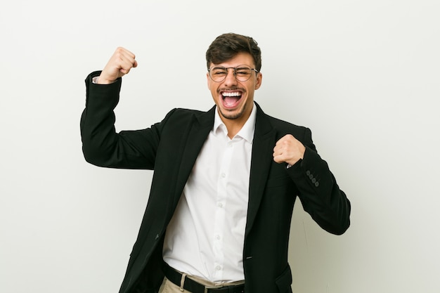 Young business hispanic man raising fist after a victory, winner .