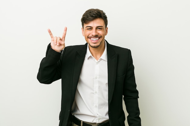 Young business hispanic man showing a horns gesture as a revolution concept.