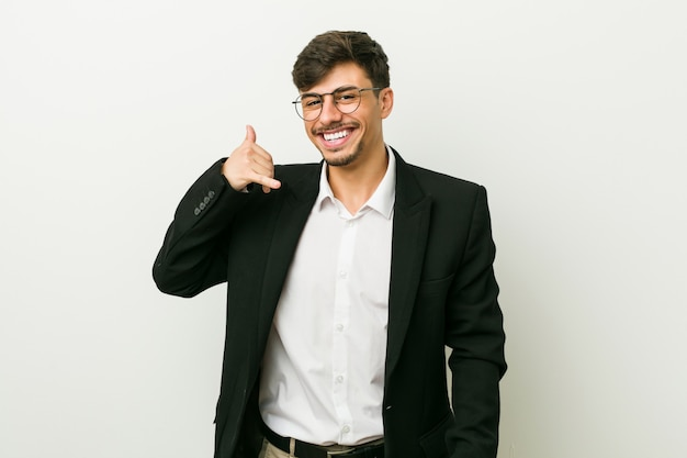 Young business hispanic man showing a mobile phone call gesture with fingers.