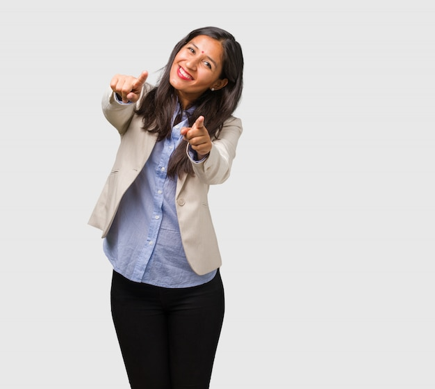 Young business indian woman cheerful and smiling pointing to the front