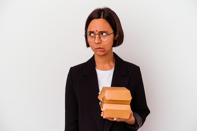 Young business indian woman eating burgers isolated confused, feels doubtful and unsure.
