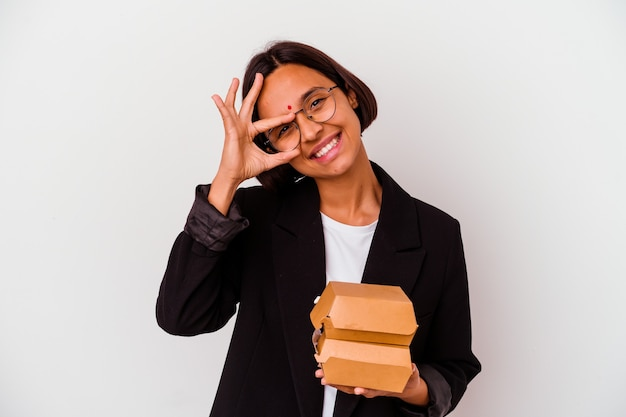 Young business indian woman eating burgers isolated excited keeping ok gesture on eye.