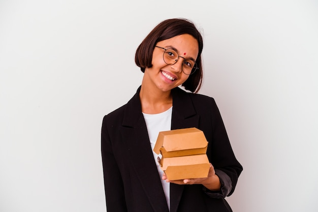 Young business indian woman eating burgers isolated happy, smiling and cheerful.