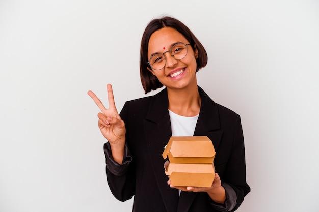 ハンバーガーを食べる若いビジネスインドの女性は、指で平和のシンボルを示して楽しくてのんきな孤立しました。