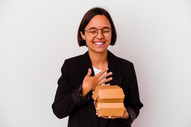 孤立したハンバーガーを食べる若いビジネスインドの女性は、胸に手を置いて大声で笑います。