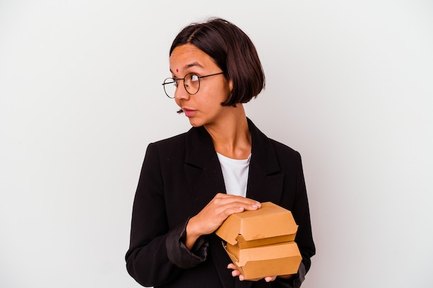 Young business indian woman eating burgers isolated looks aside smiling, cheerful and pleasant.