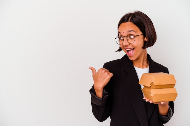 Young business indian woman eating burgers isolated points with thumb finger away, laughing and carefree.