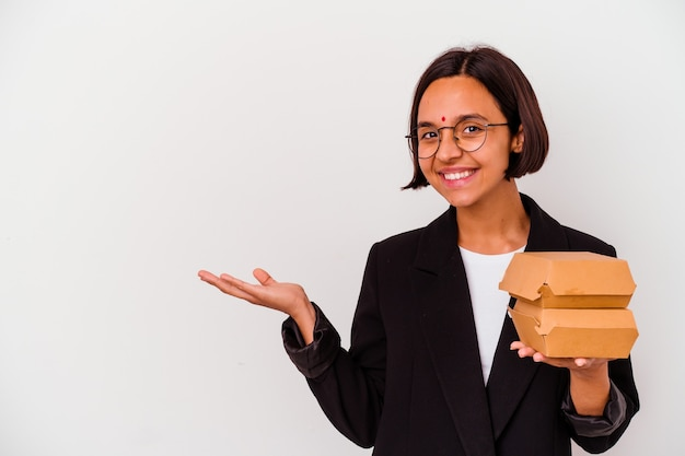 Young business indian woman eating burgers isolated showing a copy space on a palm and holding another hand on waist.