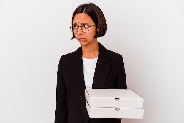 孤立したピザを持っている若いビジネスインドの女性は混乱し、疑わしく、不安を感じています。