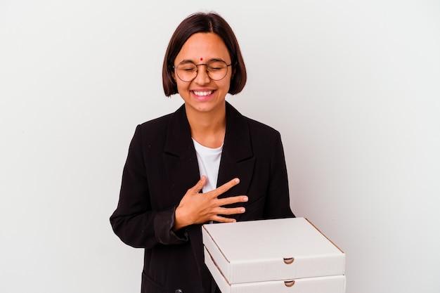 ピザを持っている若いビジネスインドの女性は、笑って楽しんで孤立しました。