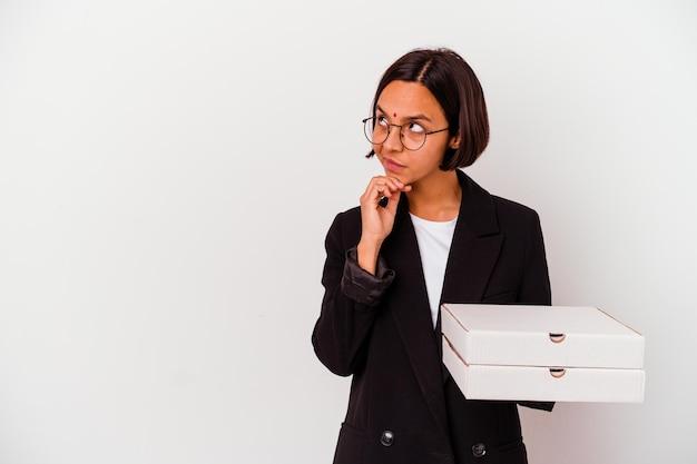 Молодая бизнес-индийская женщина, держащая пиццу, изолировала, глядя в сторону с сомнительным и скептическим выражением лица.