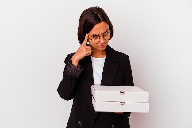 Молодая деловая индийская женщина, держащая пиццу, изолировала указательный храм пальцем, думая, сосредоточившись на задаче.