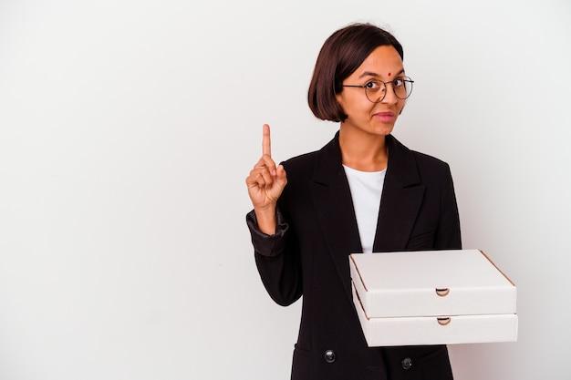 指でナンバーワンを示す孤立したピザを保持している若いビジネスインドの女性。