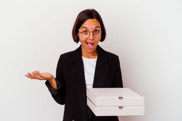 Young business indian woman holding pizzas isolated surprised and shocked.