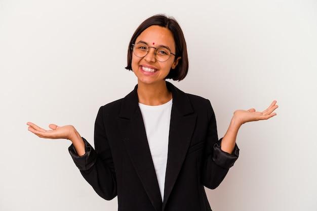 흰색 배경에 고립 된 젊은 비즈니스 인도 여자 팔으로 규모를 만들고, 행복 하 고 자신감을 느낀다.
