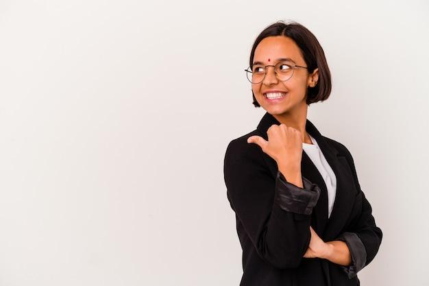 若いビジネスインドの女性は、親指の指を離れて、笑ってのんきな白い背景のポイントに分離されました。