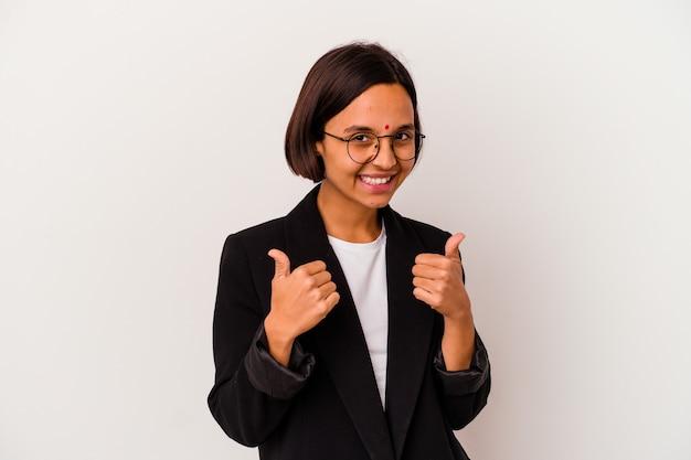 若いビジネスインドの女性は、白い背景に孤立し、両方の親指を上げて、笑顔で自信を持っています。