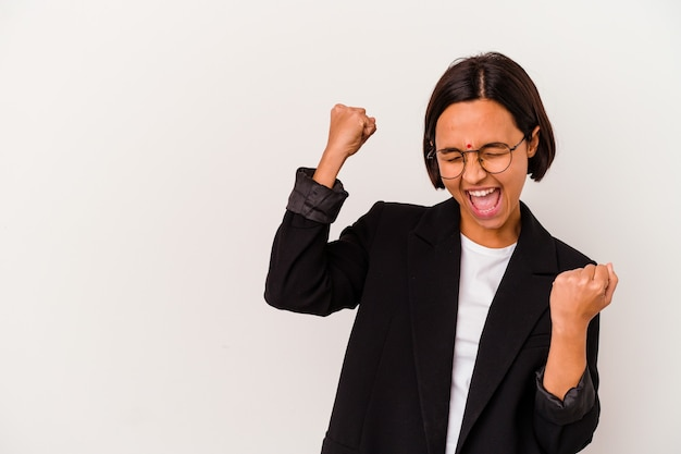 勝利、勝者の概念の後に拳を上げる白い背景で隔離の若いビジネスインドの女性。