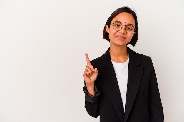指でナンバーワンを示す白い背景で隔離の若いビジネスインドの女性。