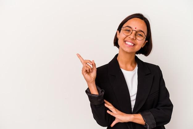 人差し指を離れて元気に指して微笑んで白い背景で隔離の若いビジネスインドの女性。