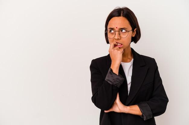 Молодой бизнес индийская женщина, изолированных на белом, расслабилась, думая о чем-то, глядя на копию пространства.