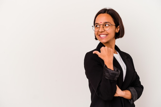 Young business indian woman isolated on white background points with thumb finger away, laughing and carefree.