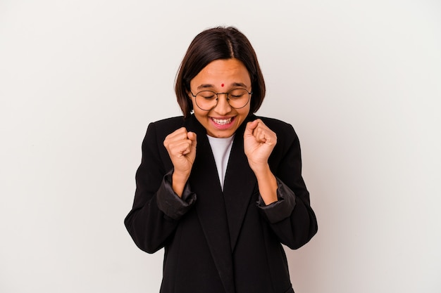 Young business indian woman isolated on white background raising fist, feeling happy and successful. victory concept.